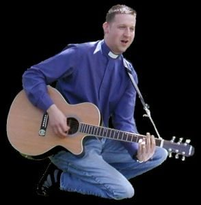 The Vicar, RevCoincidence, playing acoustic guitar